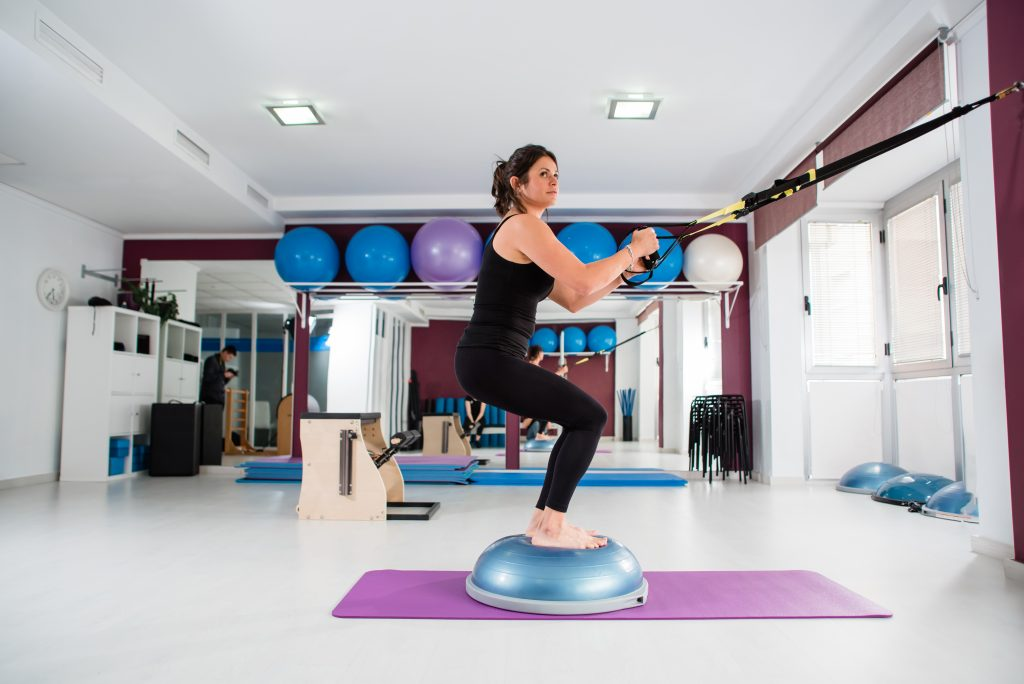 Athletic attrative young woman makes TRX exercise standing on a fitball at a gym. Active and healthy lifestyle concept.